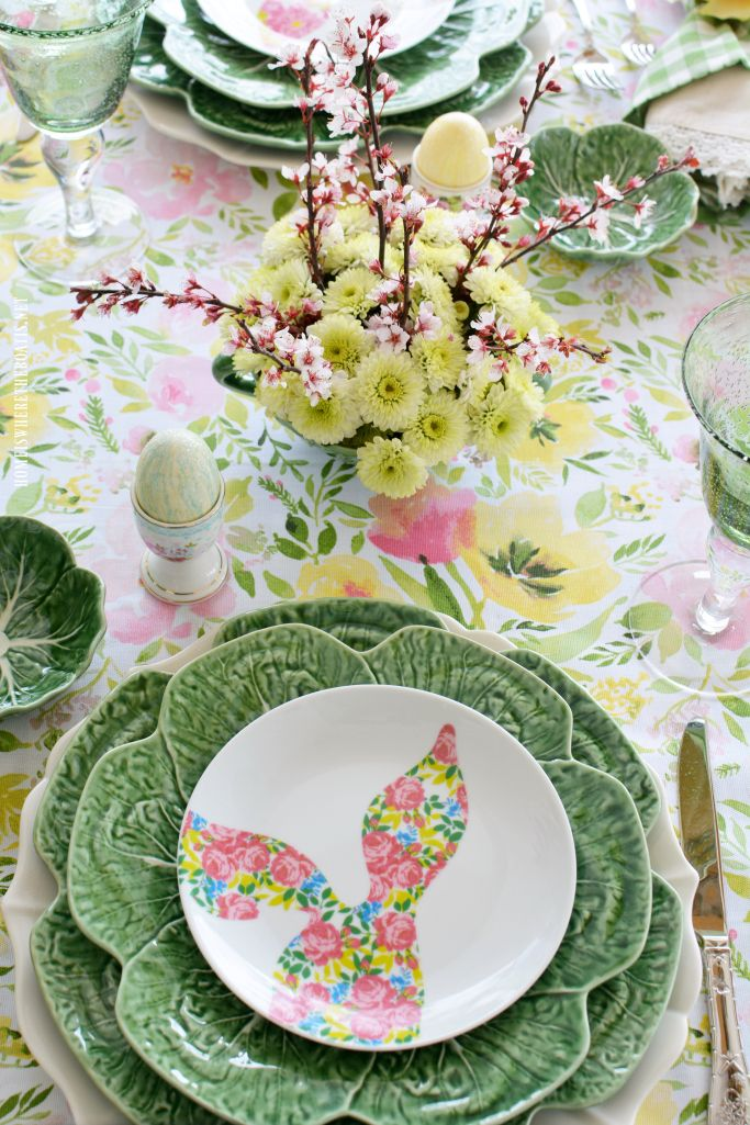 Hopping into Spring Table with pastel bunny floral salad plates, cabbage leaf chargers and glittery eggs in egg cups | homeiswheretheboatis.net #Easter #tablescape