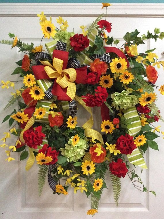 Wow your guest with this beautiful large spring or summer door wreath. This grapevine wreath is stunning with all the bright red geraniums, the black eyed susans, and green hydrangeas in it to name a few. I also used a mixture of fresh looking greenery in this wreath that