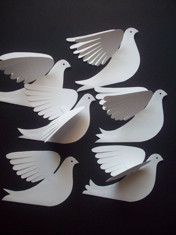Six white card stock birds that resemble doves, hand cut with slightly different details. Each is cut from folded white card stock with feather cut wings, detailed tails, a facial profile with beak and hole-punched eye. Gently bend the wings for your decorating needs. You could fasten them to a wall or hang them using the paper loop glued between the wings. Use string or fishing line or ribbon. They measure about 5.5 x 4, which is about one-fourth of a piece of standard paper.  One photo…
