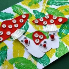 """ОСЕННИЕ ПОДЕЛКИ ДЛЯ ДЕТЕЙ. Очень интересная и красивая осенняя поделка для детей. Сначала подготавливаем фон: делаем отпечатки листочками на бумаге. Когда краска высохнет, наклеиваем на бумагу аппликацию """"Мухоморы"""". Аппликация выполнена из цветной бумаги, пуговиц, бумажной формочки для кексов, декоративных помпонов и кукольных глазок."""