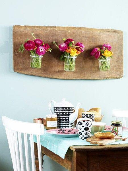 Bastelideen, für die man Sie bewundern wird: Das Holzbrett mit den kleinen Blumenvasen ist rustikal und feminin zugleich.