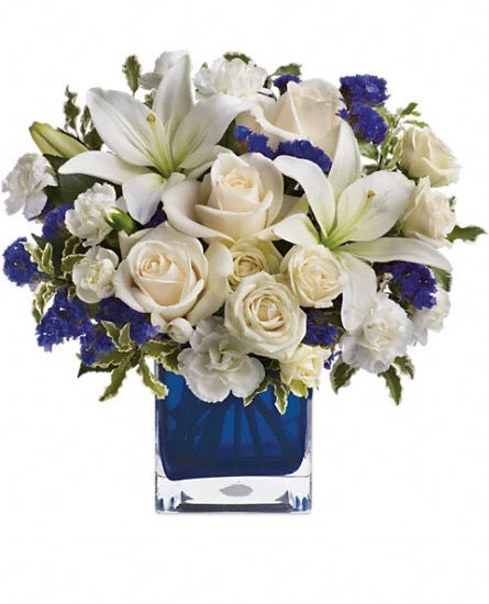 """Teleflora's Sapphire Skies Bouquet Flowers on round mirrors/for half of the guest tables.  The rest of the tables have lanterns or """"light houses"""". Add yellow Billy Buttons"""