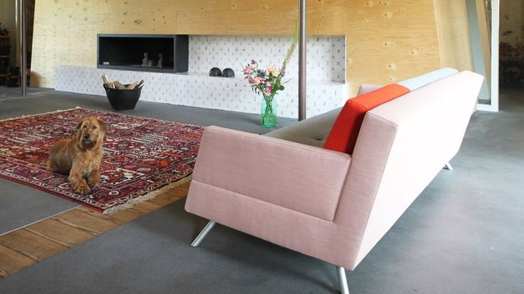 """Bij Annemariken & Geert in Berlicum (bij 's-Hertogenbosch) staat bank LOT in een opvallende kleurencombinatie: een roze-rode romp met 2 grijze kussens en een kleiner kussen in het rood - """"We zochten een neutrale bank in pittige kleuren, die iets huiselijks zou hebben maar tegelijkertijd goed op kantoor zou passen"""", vertelt Annemariken. Dat schaap met 5 poten bleek LOT uit de basiscollectie van VRIENDEN."""