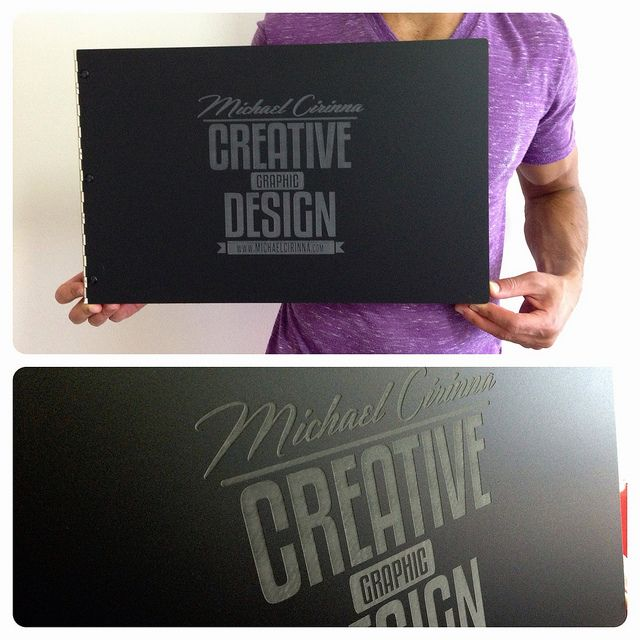 custom graphic design portfolio book with engraving treatment on matte black acrylic