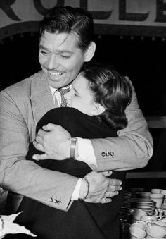 """Clark Gable hugs Judy Garland at an informal birthday party in his honor on the set of Test Pilot, where the young star sang a version of her song """"Dear Mr. Gable."""" To add to the celebration, Gable had also just been officially crowned """"King of Hollywood"""" by Ed Sullivan and the New York Daily News—a title that epitomizes him to this day."""
