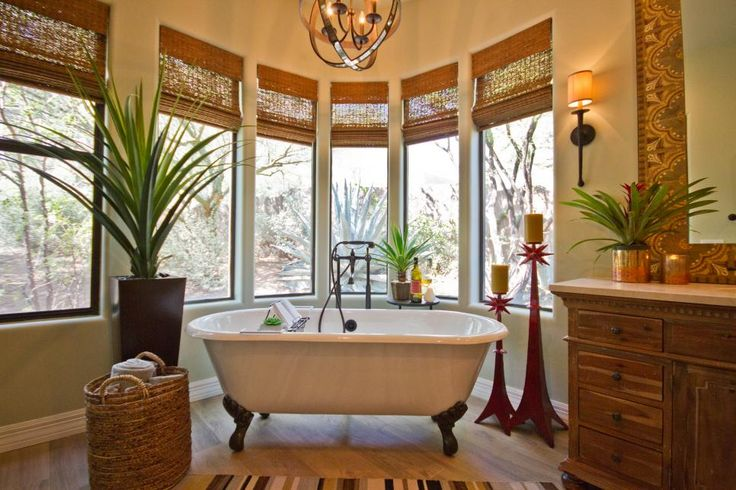 This beautiful and luxurious Southwestern design features a white clawfoot bathtub perfect for relaxing and enjoying the outdoor view. Potted plants bring natural color and life to the room, while spiked red candlesticks add personality.