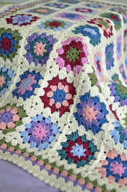Granny square blanket inspiration colorful muted tones on the inside with a white border.