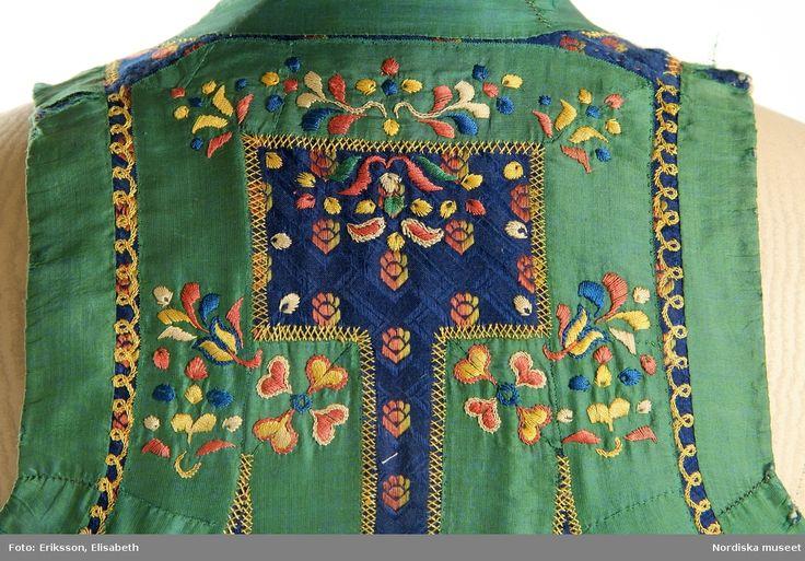 Livkjol med kjol av blåsvart vadmal. 3 våder, den främre slät, bakvåderna goffrerade, helfodrad med blekt fintrådig linnelärft. Sprund mitt fram. Kort liv av halvsiden, blå mönstervävd botten med strödda stiliserade blommor liknande tassavtryck i gult och orange silke. 2 framstycken och 1 ryggstycke. Runt hals, ärmhål, framkanter och över nästan hela ryggen pålagda gröna sidenband 3 cm breda, på och runt banden broderi med silke i vitt, rosa, gult och blått med plattsöm. och flätsöm. Live...