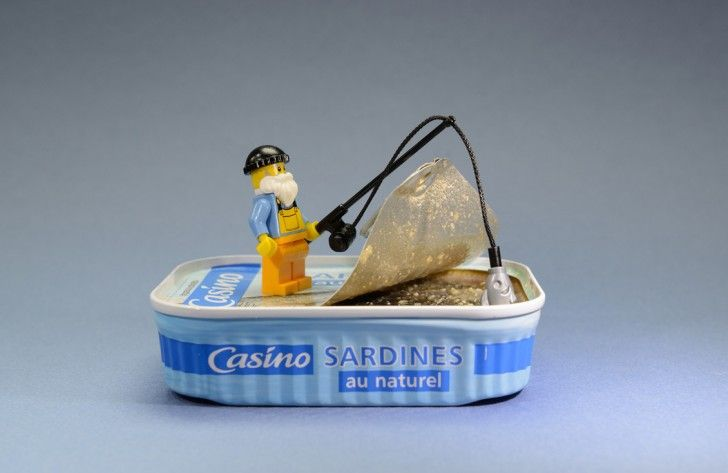 Real-life lego minifigure of a man fishing in a can of Sardines