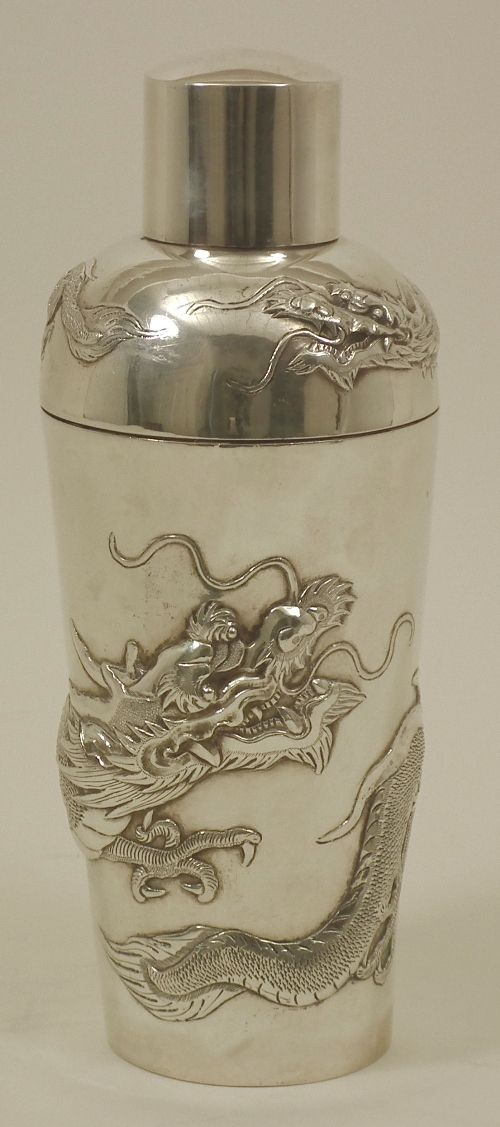 An early 20th Century Chinese silver cocktail shaker, the tapered body boldly embossed and engraved with a dragon, - December 2010 SOLD FOR: £ 500