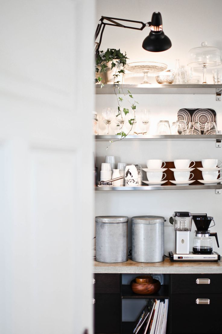 Inexpensive IKEA shelving substitutes for upper cabinetry and an iconic office lamp becomes task lighting in this chic, industrial kitchen.: