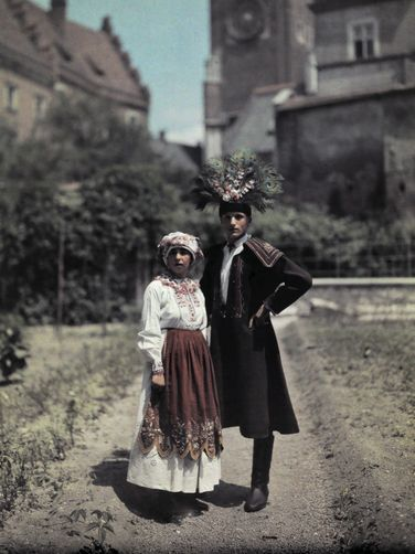 Portrait of a bride and groom; hat is adorned with feathers for luck
