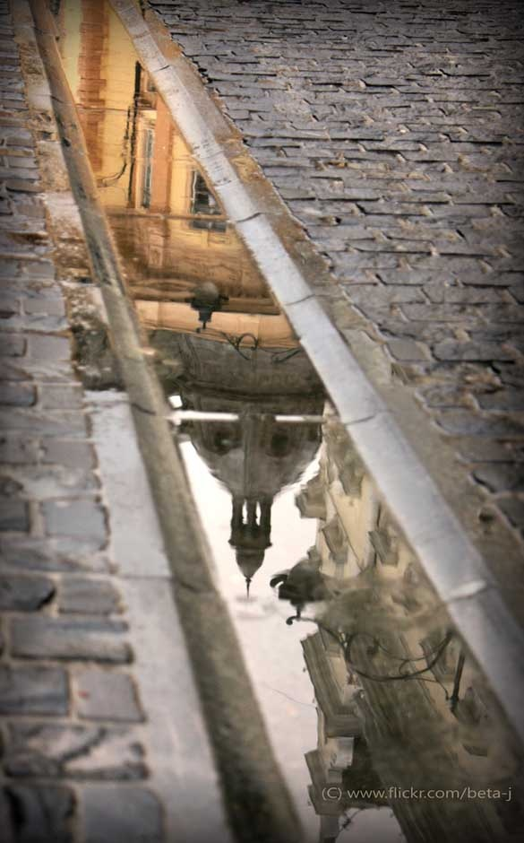 Wet cobblestones reflecting a church. Reminds me of life in Europe...