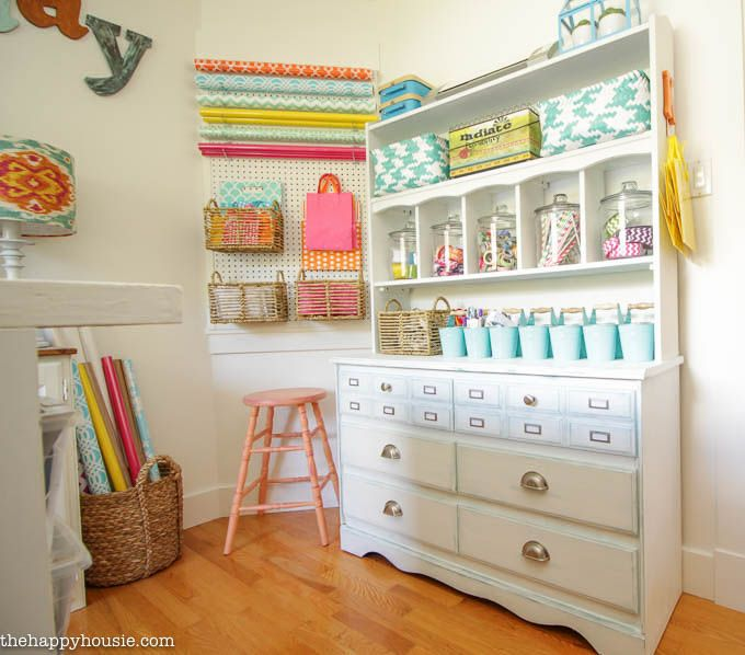 Colorful Cheery Craft Room Tour at The Happy Housie   Love those huge jars! A fun & pretty way to display colorful craft supplies.