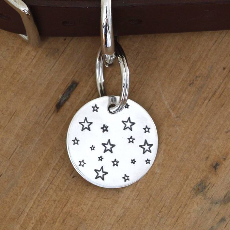 A hand-made, stylish silver dog tag with a galaxy of stars on the front, and ID information on the back.This evocative dog tag is perfect for the star in your life, and a treasured gift for dog-owning family and friends. You can choose two IDs for the back of your tag: First ID: (for example) your phone number Second ID: (for example) second phone number / house no. & postcode / I am chipped Your dog tag is supplied with a secure split-ring attached, and carefully gift-wrapped. All silver…