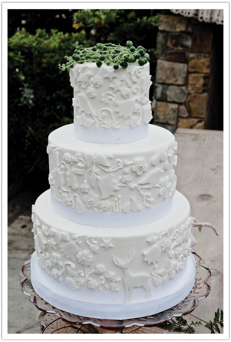 White on white wedding cake. Cut-outs can be customized to all things important to the bride and groom (this one's decorated with Scandinavian symbols)
