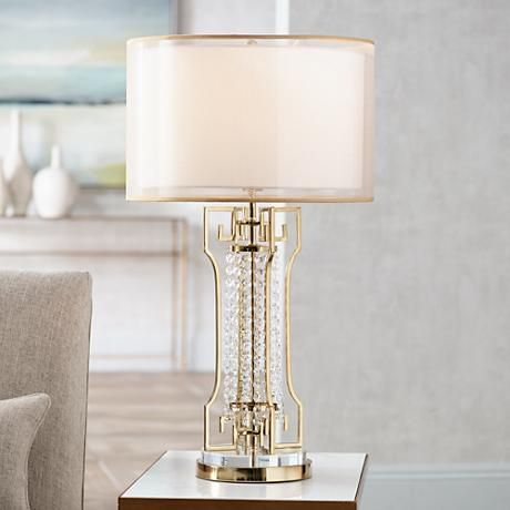 A traditional table lamp with ornate glass bead details and a double sheer drum shade on top.