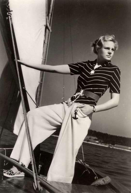 Digitalt Museum - Flicka i vida ljusa byxor med ankare på fickorna och mörk tröja med ljusa rändet håller i bom på segelbåt. Stranddräkter p...