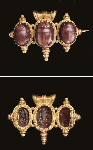THREE ETRUSCAN CARNELIAN SCARABS   Circa 4th Century B.C.   Each beetle carefully detailed, the underside of each engraved in the a-globolo style, one with a figure riding a stag; one with Herakles on a raft of four amphorae; and one with a running panther, its head turned frontal; mounted together as a brooch in a late 19th century gold 'Classical Revival' setting, recalling the work of the Italian jewelers Castellani and Giuliano  11/16 in. (1.7 cm.) long (largest)