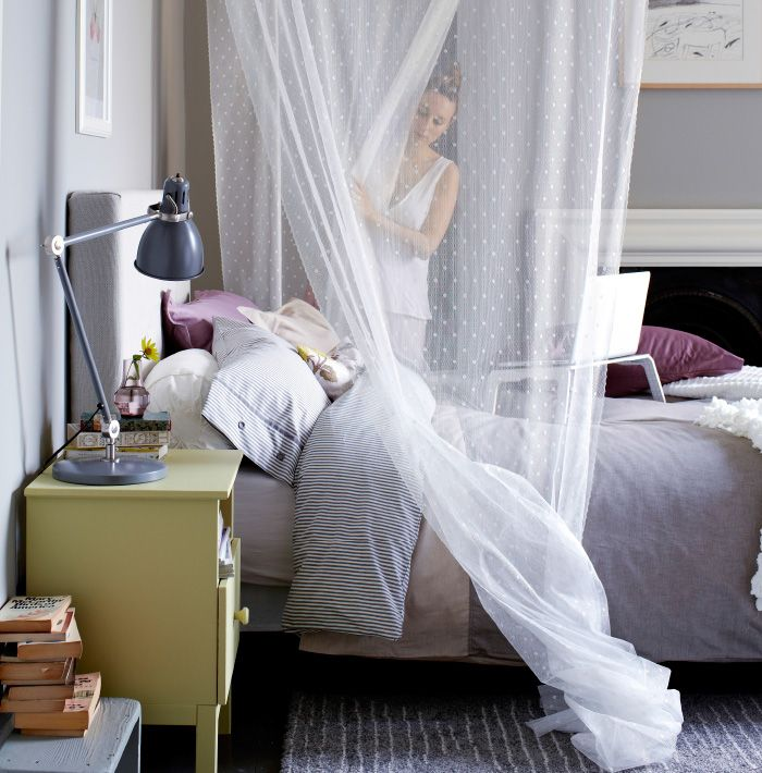 View bed with layers of textiles, a laptop table on bed, soft fabric draped overhead, yellow bedside table and grey lamp in foreground.