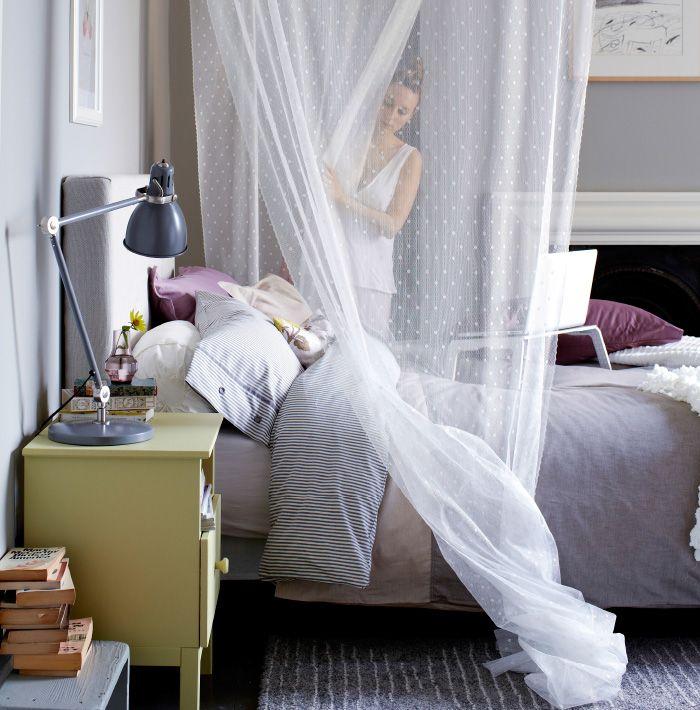 Camera da letto con tessili, tenda drappeggiata, supporto per PC portatile, comodino giallo e lampada grigia.