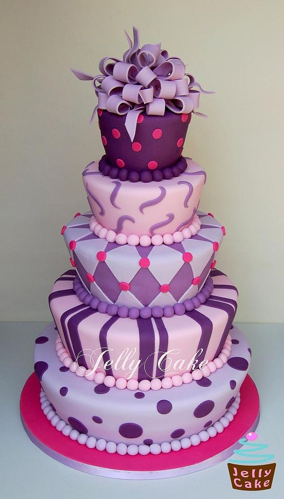 Purple tiered cake with multiple designs (It reminds me of Alice in Wonderland!)