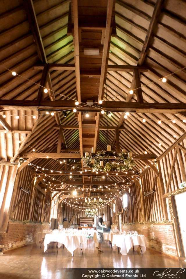 Festoon lights hung in relaxed crosses all the way down the barn at Lillibrooke Manor- perfect for rustic and vintage wedding styles