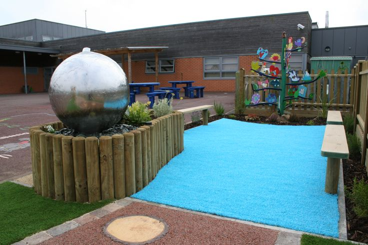 "Far end of the garden houses our ""values tree"", a seating area and the interactive water feature that the children can touch and turn on & off as they wish."
