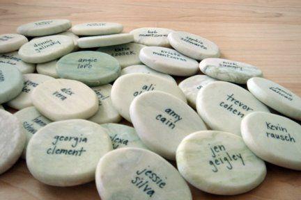 Witte stenen naamkaartjes voor tafelschikking. Steen op menu op servet op bord (voorkomt wegwaaien menukaart)