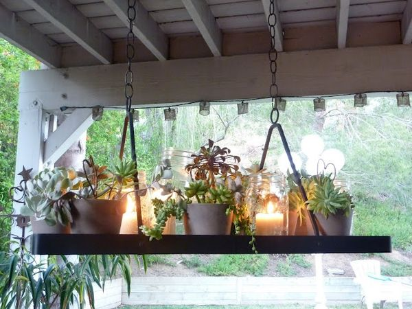 DIY Gardens for Small Spaces - created from a kitchen pot rack. Together, the mini garden of succulents and the simple white candles create a romantic and timeless ambiance for any porch or sheltered patio.