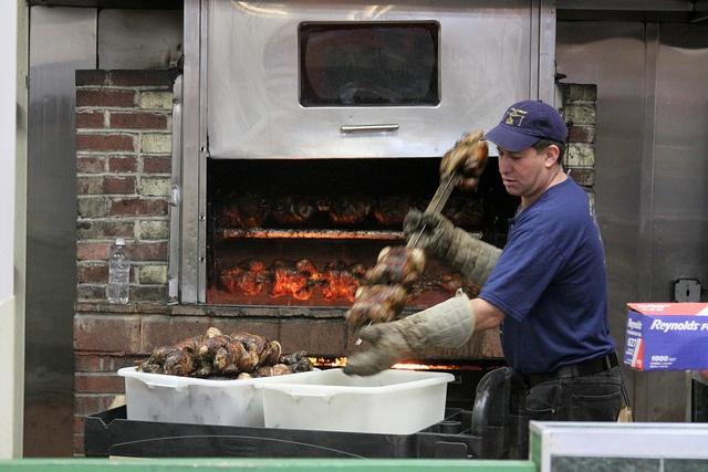 Pulling chickens from the roaster at El Pollo Rico in Arlington, VA