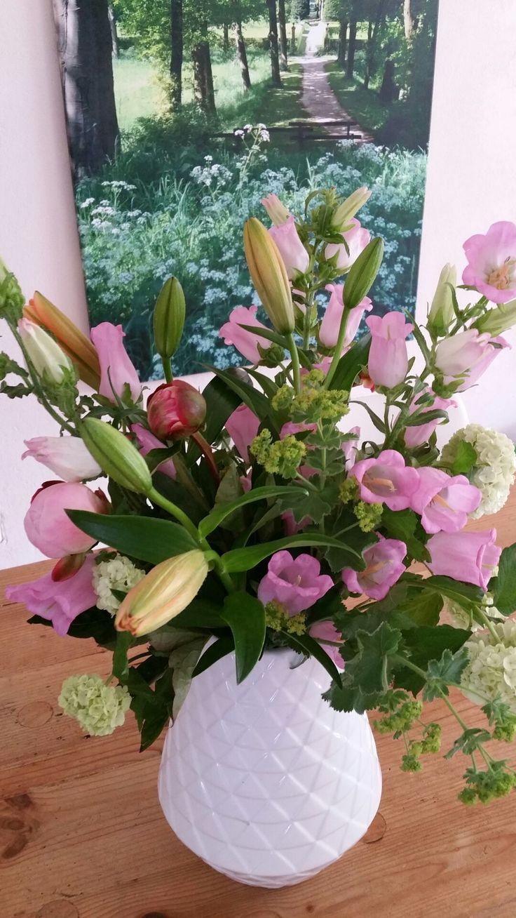 Oranje lelie, campanula, pioenrozen, vrouwenmantel en viburnum voor een weelderig boeket
