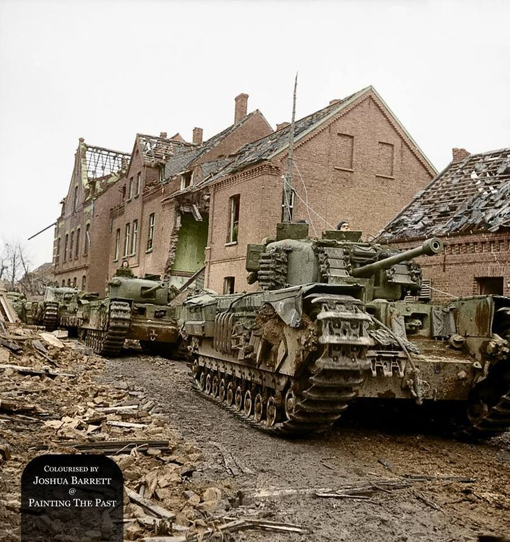 Churchill tanks of the 6th Guards Tank Brigade supported by infantry of the 2nd Gordon Highlanders (seen in windows of the large ruin) drive along a badly damaged street in Kleve, Germany. 12th February 1945