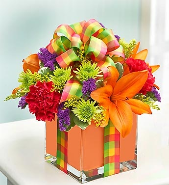 All Wrapped Up™- arrangement of orange lilies, hot pink carnations, poms, solidago, statice and variegated pittosporum $49.99- $54.99 #presents #birthdayflowers #birthdaypresents