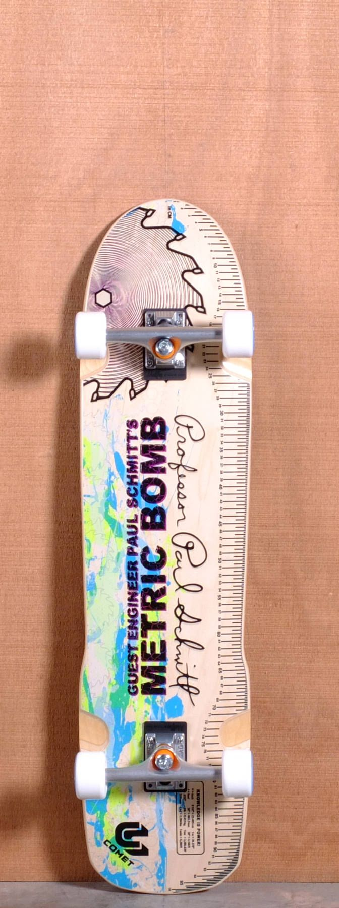 """The Comet Paul Schmitt Metric Bomb Longboard Deck is designed for freeride, Sliding and Pool skating. Ships fully assembled and ready to skate!  Function: Freeride, Sliding, Pool  Features: Concave, Rocker, Symmetrical Platform, Upturned Nose, Kicktail, Wheel Wells  Material: Air-Frame Construction, Corrugated Maple Ply  Length: 38""""  Width: 9.25""""  Wheelbase: 20""""  Thickness: 9/16""""  Hole Pattern: Old School  Grip: None"""