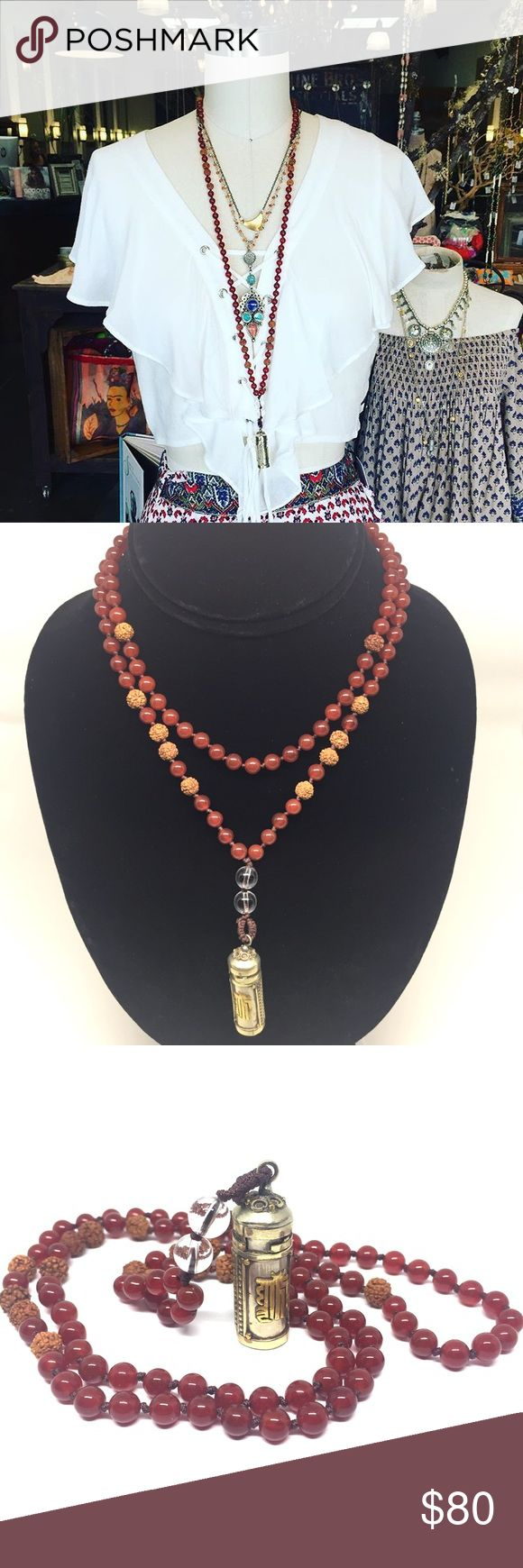 Action Mala Necklace Beautiful carnelian mala necklace with 108 genuine carnelian gemstones and Rudruksha seed beads. Necklace is complete with a Nepalian pendant that opens. One can place a handwritten mantra or intention inside for safekeeping. Necklace measures 28 inches around and beads are 6 mm. Jewelry Necklaces