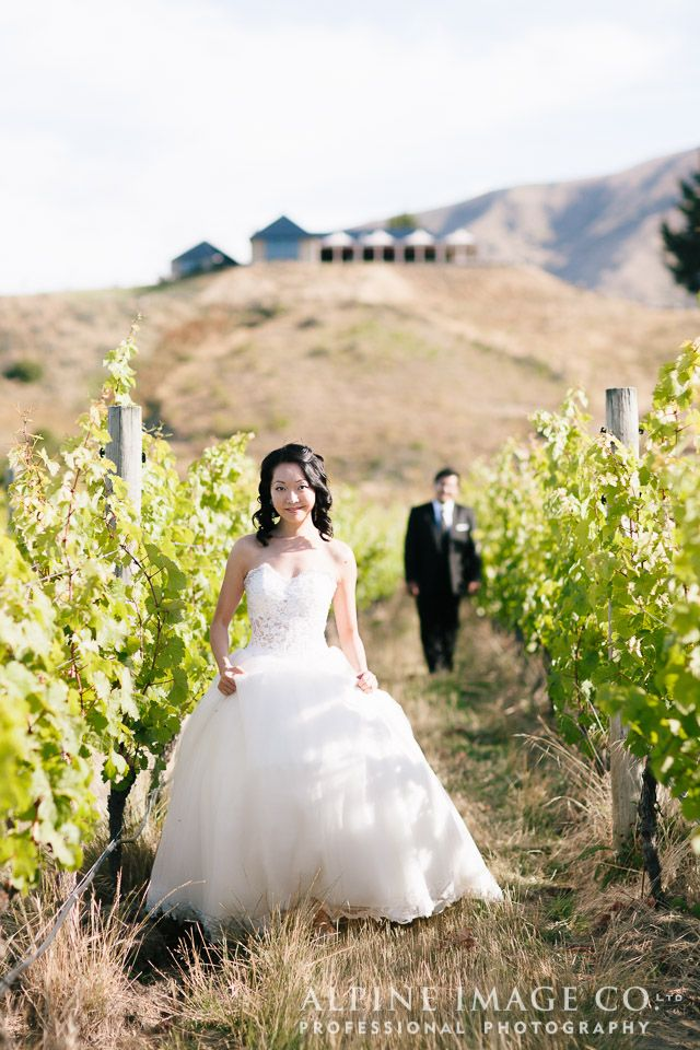 The happy couple amongst the vines at Rippon, Lake Wanaka