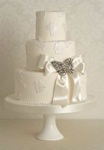 Small white wedding cake with lovely brooch and white bow detail.       ᘡղbᘠ