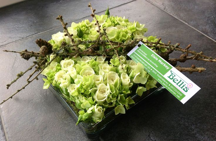 Modern bloemstuk met witte trosroosjes.