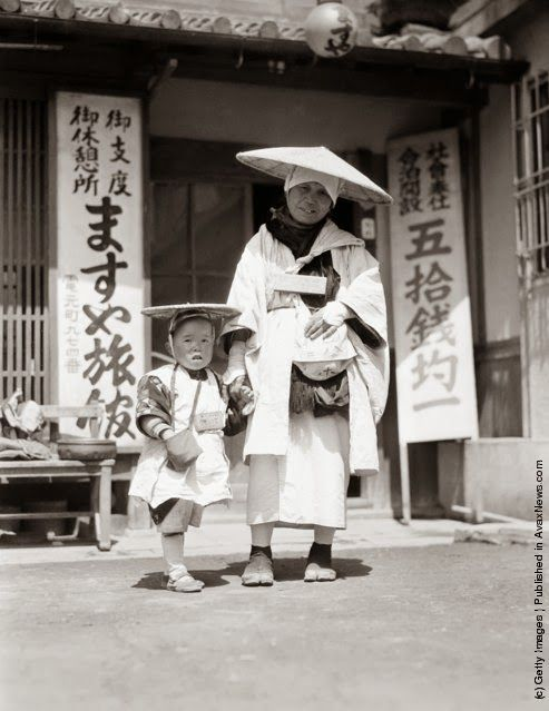 Buddhist pilgrim mother and child wearing traditional costume, begging for donations, Kobe. (Photo by Charles Phelps Cushing/Retrofile/Getty Images). Circa 1930s