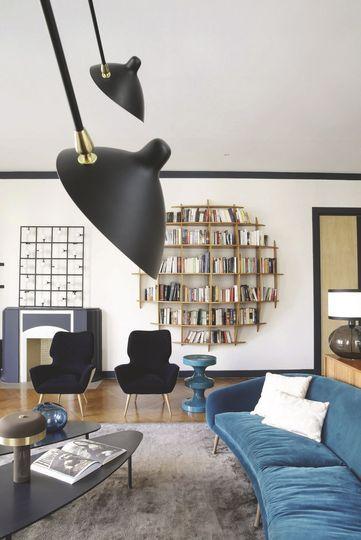 plinthe noire entourant sol plafond + canapé bleu
