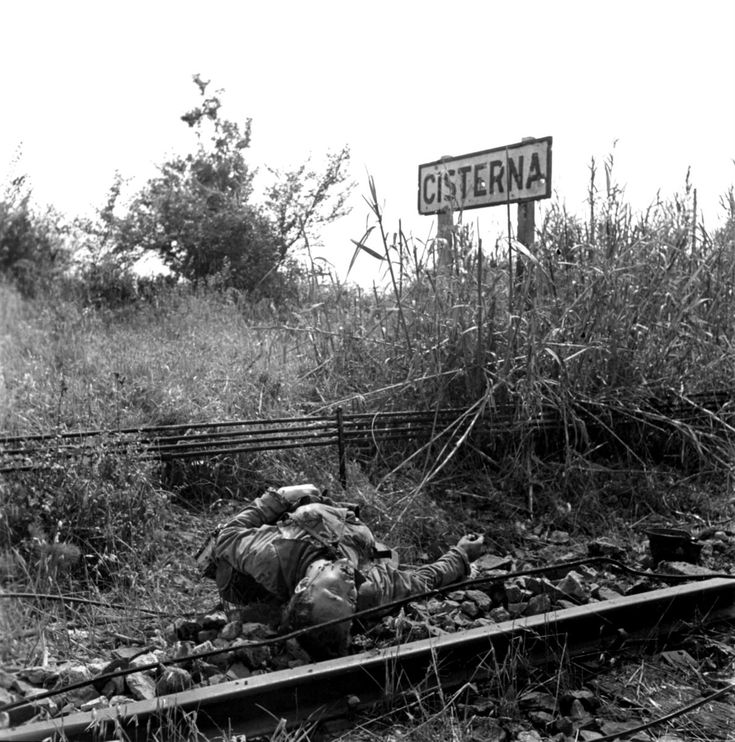 The corpse of a German Wehrmacht soldier killed in action lies beside the railroad tracks in front of the signpost of the village of Cisterna di Latina after the Allies eventually took the area in May 1944. Earlier that year, the Allies launched the unsuccessful the Battle of Cisterna in an effort to break out of the Anzio beachhead before German reinforcements could arrive and concentrate for a counterattack. The result was a German victory. Cisterna di Latina, Province of Latina, Lazio…