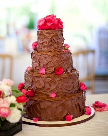 Four-tier chocolate cake decorated with ranunculus and flower petals