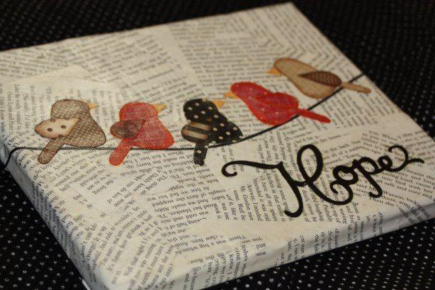 Een schilder doek waarvan je het beplakt hebt met papier met letters erop en dat heb je erop geplakt met behangerslijm. En van stof gemaakte vogeltjes erop gekleeft.