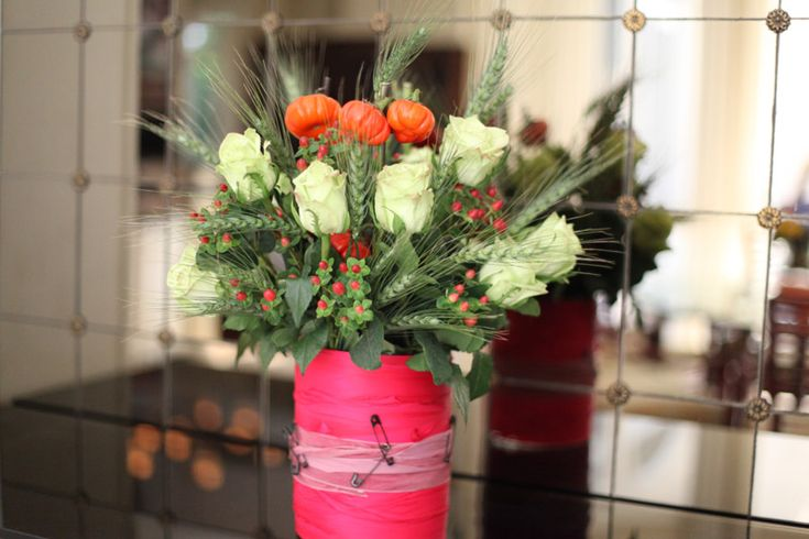 The vase of the floral arrangement was inspired by Tom Binns. I really love the color combo; hot pink ribbon, orange pumpkin plants, the red-pink hue of the filling flowers, and the white stone hue of the roses. It's an unexpected color combo for a floral arrangement.