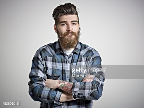 Portrait of bearded young male hipster in blue check shirt with tattooed arm looking straight to camera.
