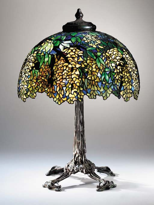 A 'LABURNUM' LEADED GLASS AND BRONZE TABLE LAMP   Tiffany Studios, circa 1910   28in. (71.1cm) high, 21½in. (54.6cm.) diameter of the shade, with finial  the shade stamped TIFFANY STUDIOS NEW YORK 1539, the 'organic root' base stamped TIFFANY STUDIOS NEW YORK