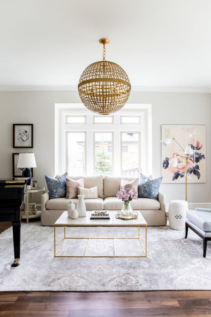neutral beige living room with touches of pink and rose gold, love the coffee table and the big grey rug
