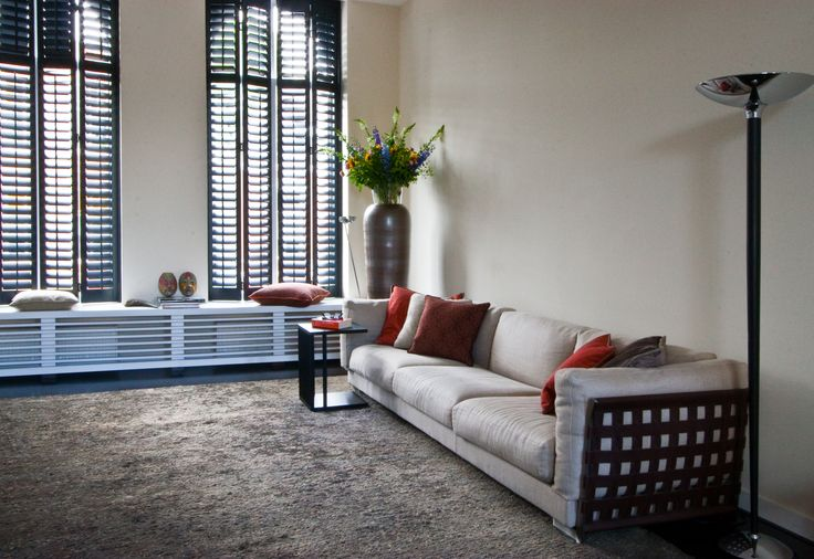 Interieur in warme aardetinten. Bank van Flexform gecombineerd met stoer hennep vloerkleed. Shutters laten de hoge boogramen zichtbaar. De radiatorombouw creëert een gezellige windowseat.