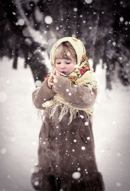 Little girl in the snow, long taupe coat with wide fur trim at bottom, pale yellow with red and green design scarf, precious